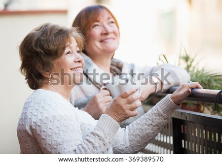 Mature women in pullovers having cup of tea on terrace - stock photo