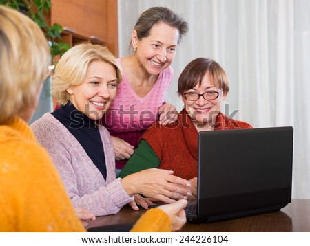 Mature women making accounts on date site in the room at the home - stock photo