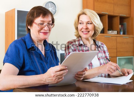 Mature women notary helping aged client drawing up of will - stock photo
