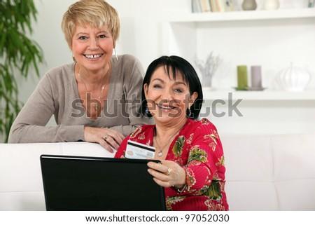 Mature women using a credit card online - stock photo