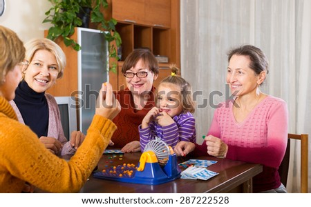 Mature women  with child having fun with table game indoor - stock photo