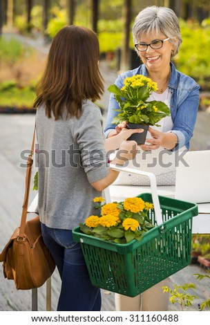 Mature women working in a flower shop and talking with a customer - stock photo