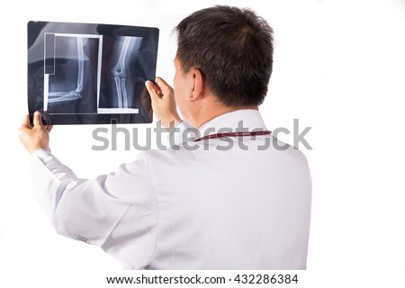 Matured Asian orthopedic medical doctor examining X-ray film on white background - stock photo