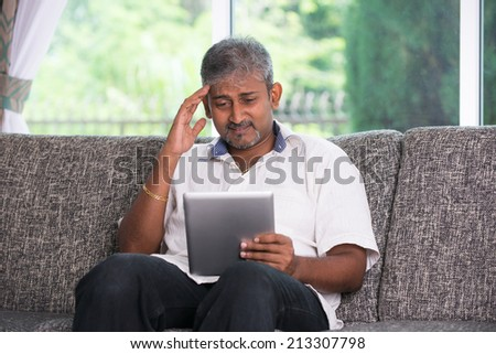 matured indian male in stress worry look with a tablet on a sofa setting - stock photo