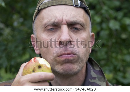 Matured man chewing apple with a doubtful look at his face, outdoor horizontal shot