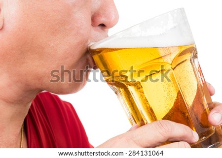 Matured man drinking a large mug of cold refreshing beer - stock photo