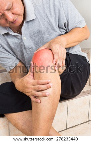 Matured man suffering from painful knee joint seated on steps - stock photo