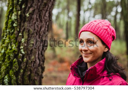 Matured woman with wool pink hat in the forest