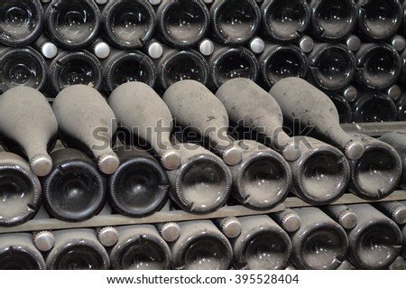 Maturing in dusty champagne bottles in the wine cellars of the factory of sparkling wines, the focus at the top - stock photo