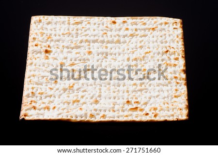 Matzo - A traditional Jewish Passover bread on a black background - stock photo