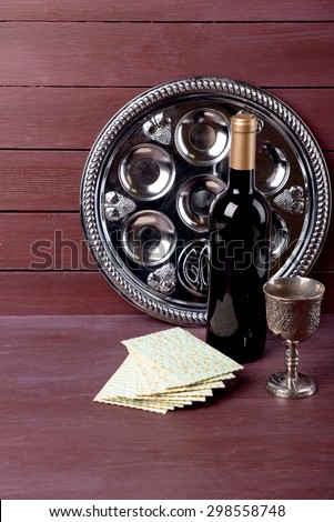 Matzo for Passover with metal tray and wine on wooden background - stock photo