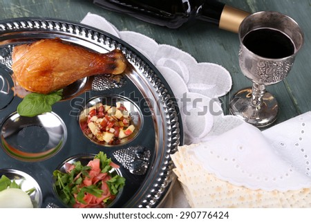 Matzo for Passover with Seder meal and wine on plate on table close up - stock photo