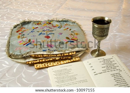 matzo in an antique embroidered matzo cover with kiddush cup of wine and traditional passover haggadah text