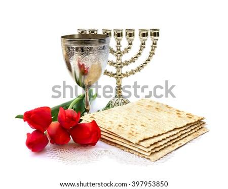 Matzo, wine, menorah and red tulips for passover celebration on white background - stock photo