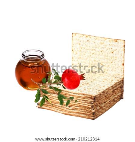 Matzoh ( matzah or matzo is bland flat dry bread), ripe pomegranate and honey - jewish traditional festive food symbols. White isolated  - stock photo