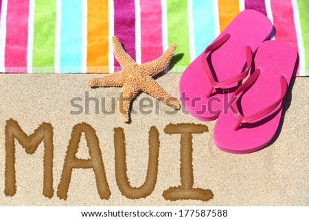 Maui, Hawaii beach travel concept. Maui written in sand with water next to beach towel, summer sandals and starfish. Hawaiian vacation holidays - stock photo