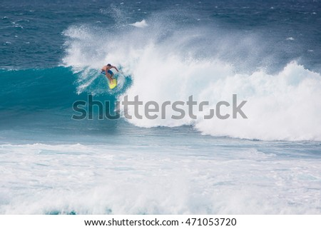 MAUI, HI - MARCH 17: A guy rides big waves at Hookipa Beach March 17, 2015, in Maui, Hi.
