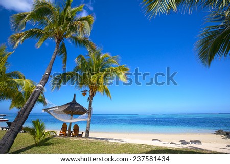 Mauritius beach with chairs and umbrellas - stock photo