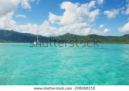 Mauritius Island - Boat catamaran on Water turquoise - Sea and Mountains - stock photo