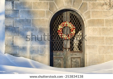 Mausoleum with a Christmas wreath on the door sits silently in the deep snows of Winter.  - stock photo