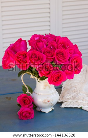 Mauve blooming  roses in vase  bouquet on a blue  table