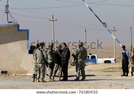 MAXMUR CITY, IRAQ - JANUARY 26: Unidentified USA soldiers stands guard in a check point on January 26, 2007 in Maxmur, Iraq. - stock photo