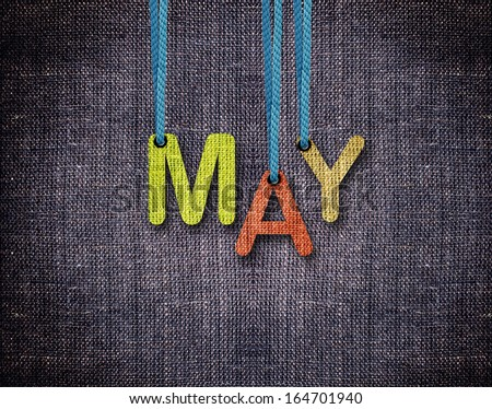 May letters hanging strings with blue sackcloth background. - stock photo
