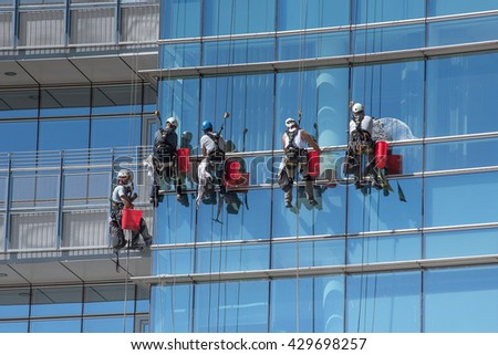 May 24, 2016 Milan, Lombardy, Italy : Group of window cleaners cleaning the external glass facade of a skyscraper