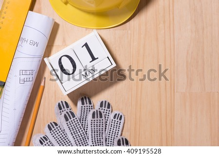 May 1st. Image of may 1 white blocks wooden calendar with construction tools on the table. International Workers' Day. Labor day concept. Copy space view from above - stock photo