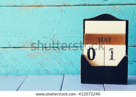 May 1st. Image of may 1 wooden calendar over blue wooden background. Spring day,  International Workers' Day, Happy May Day . room for text - stock photo