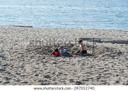MAY 15TH 2015, Seattle: a group of children playing on the Alki beach in a sunny day, Seattle WA - stock photo