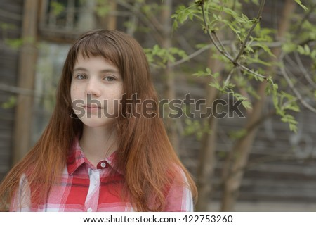 MAY 2016, the girl the teenager in a red shirt and jeans walks in the yard with the blossoming cherries