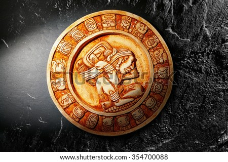 Mayan calendar carved in stone on dark background - stock photo