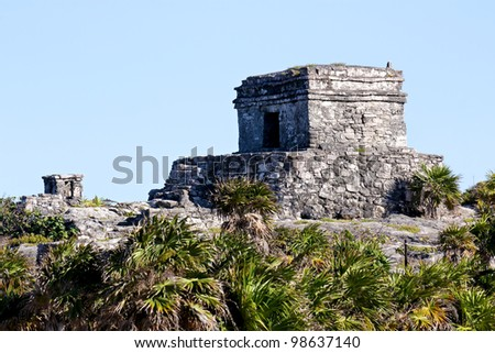 Mayan ruins in the sun before a clear blue sky at Tulum, Quintana Roo, Mexico. - stock photo