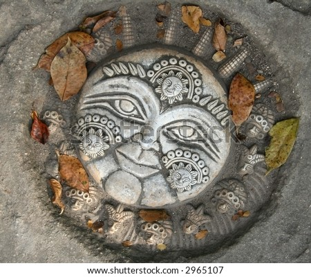 Mayan sun stone sculpture on pavement with leaves - stock photo