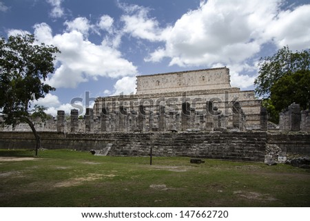 Mayan temple and columns in the jungle - stock photo