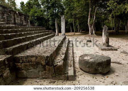 Mayan temple in the jungle with stelas  - stock photo