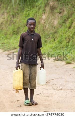 MAYANGE; RWANDA - NOVEMBER 4: Unidentified boy carries a large water jug to get water at November 4; 2013. - stock photo