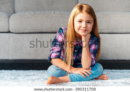 Maybe play? Cheerful little girl looking at camera with smile while sitting on the carpet in lotus position at home - stock photo