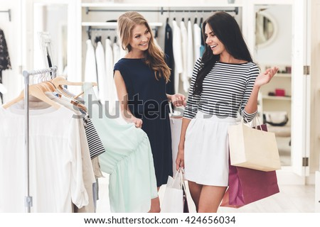 Maybe this dress? Two beautiful women with shopping bags looking at each other with smile while standing hear hanger at the clothing store - stock photo