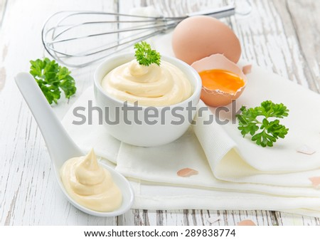 Mayonnaise in bowl on wooden table. - stock photo