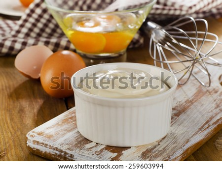 Mayonnaise in  bowl with eggs  on a wooden background. - stock photo