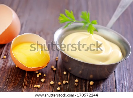 mayonnaise in metal spoon on wooden board - stock photo