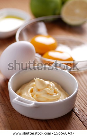 mayonnaise sauce with ingredients on wooden table