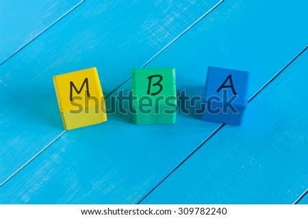 MBA or Master of Business Administration sign on wood children's colourful cubes or blocks and blue wooden background - stock photo