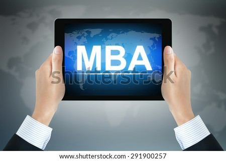 MBA sign on tablet pc screen held by businessman hands - online MBA concept