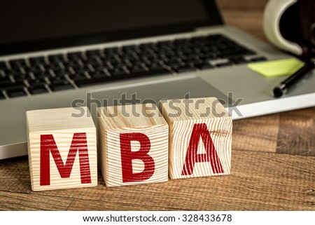 MBA written on a wooden cube in front of a laptop - stock photo