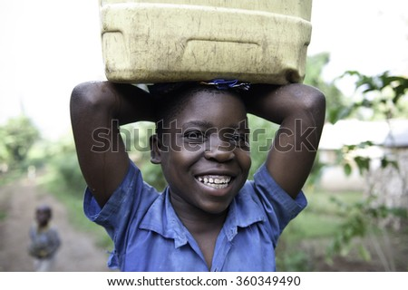 MBALE, UGANDA - NOVEMBER 15, 2013: A young girl is carrying water in Nabugoye Hill, a rural area close to Mbale.  - stock photo