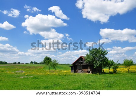 Meadow and abandoned wooden cabin against blue sky