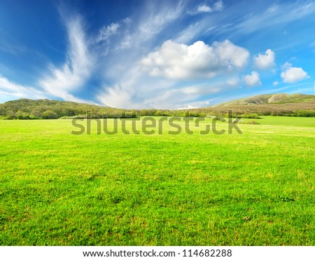 Meadow and sky with bright clouds. Mountain valley and plain
